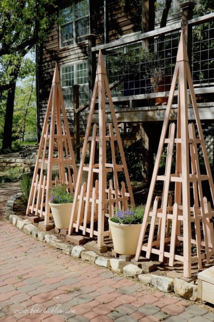 Three French Country Trellis Tuteurs in a Narrow Flower Garden